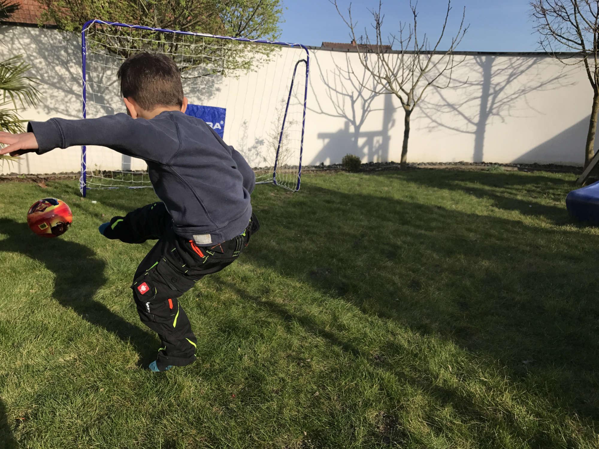 Kind schießt auf Fußballtor im Garten