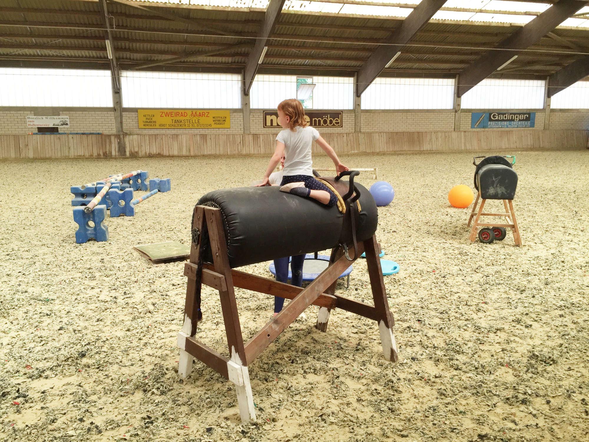 Hobbies für Kinder Voltigieren Kind auf dem Holzpferd zum üben