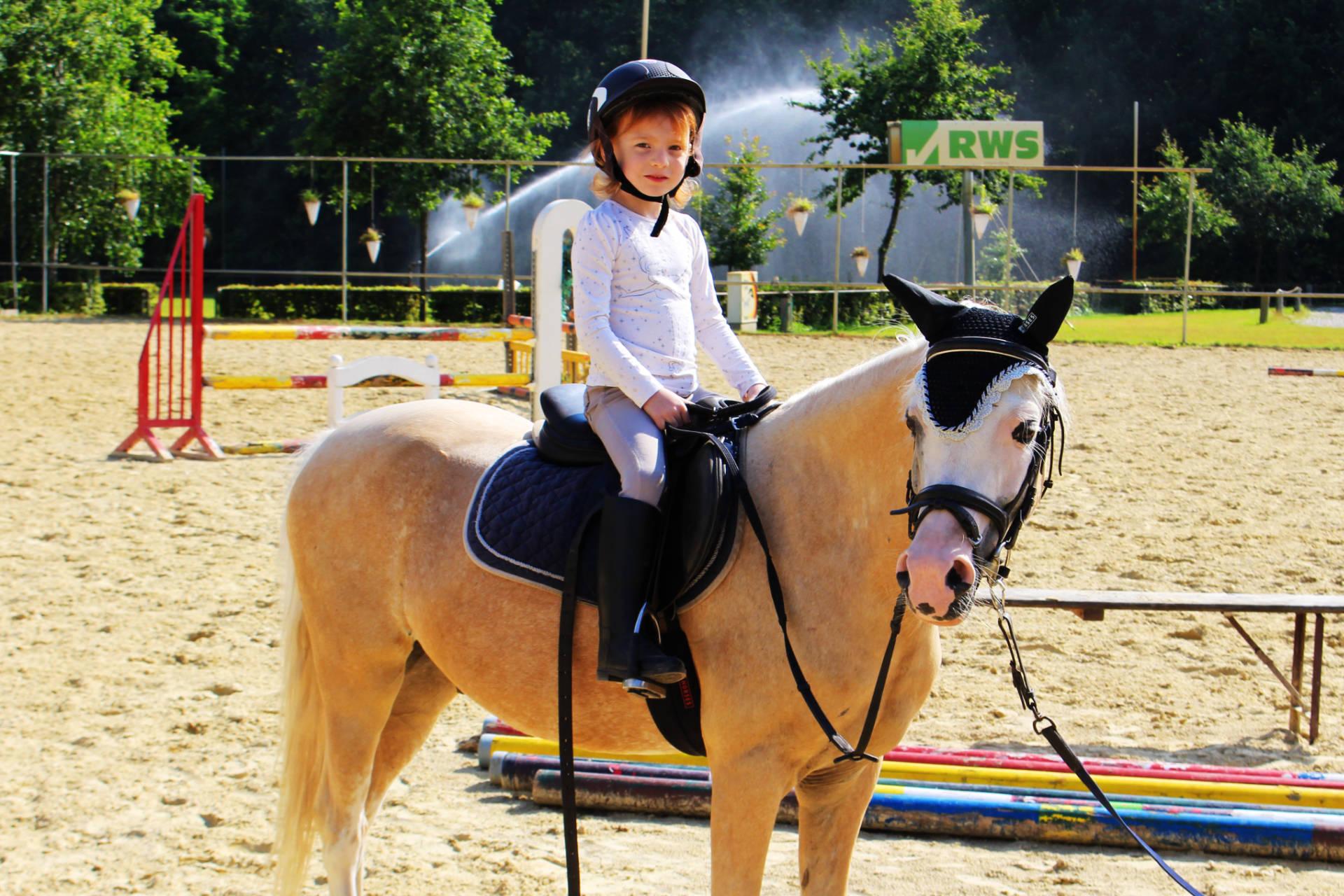 Hobbies für Kinder - Nala sitzt auf ihrem Pferd Euki mit Sattel und Reithelm